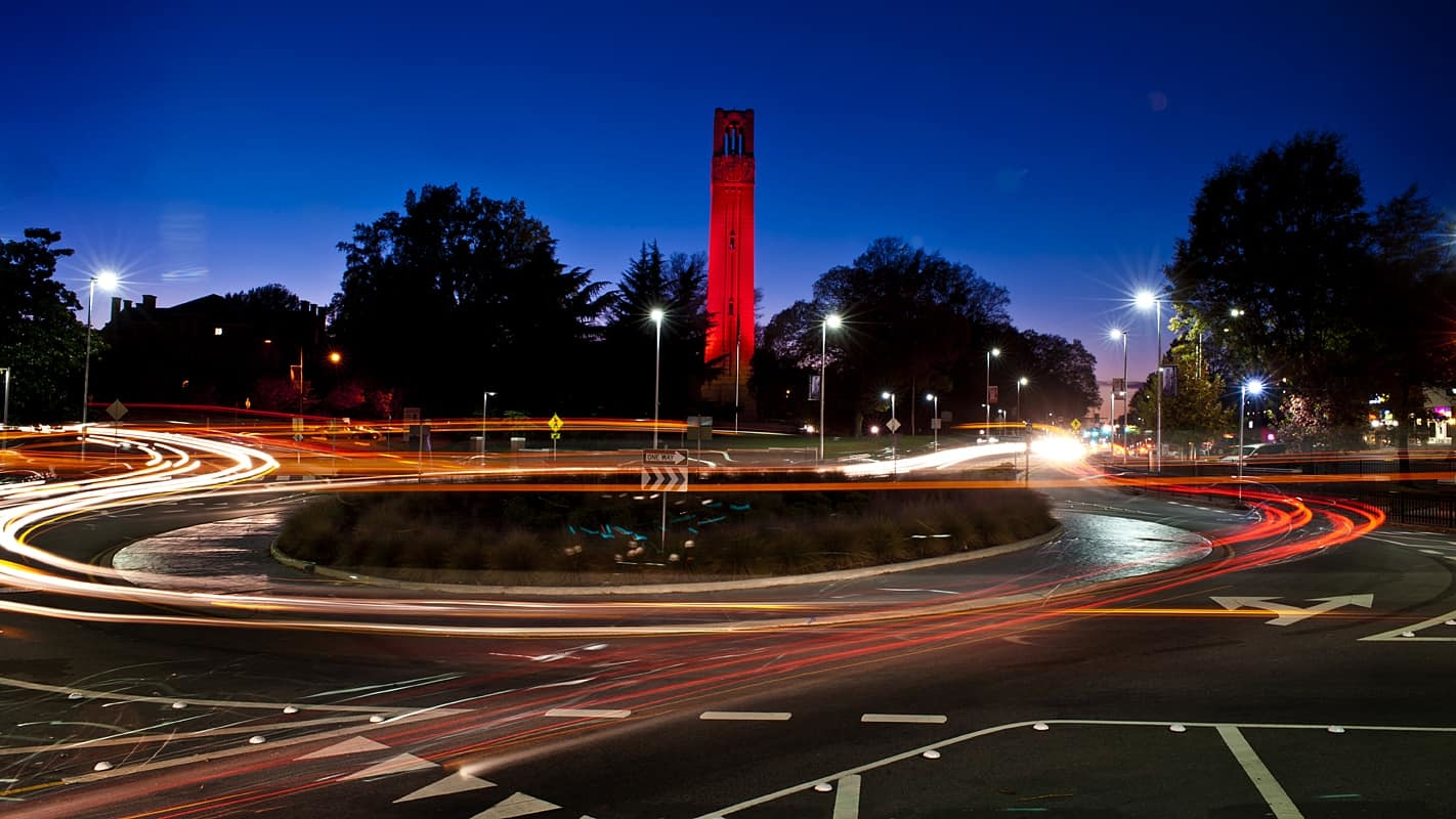 NC State Belltower lit red at night with the Hillsborough Street traffic circle in the foreground
