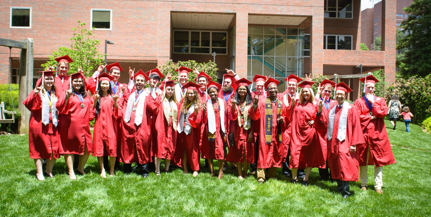 Graduate students in red caps and gowns