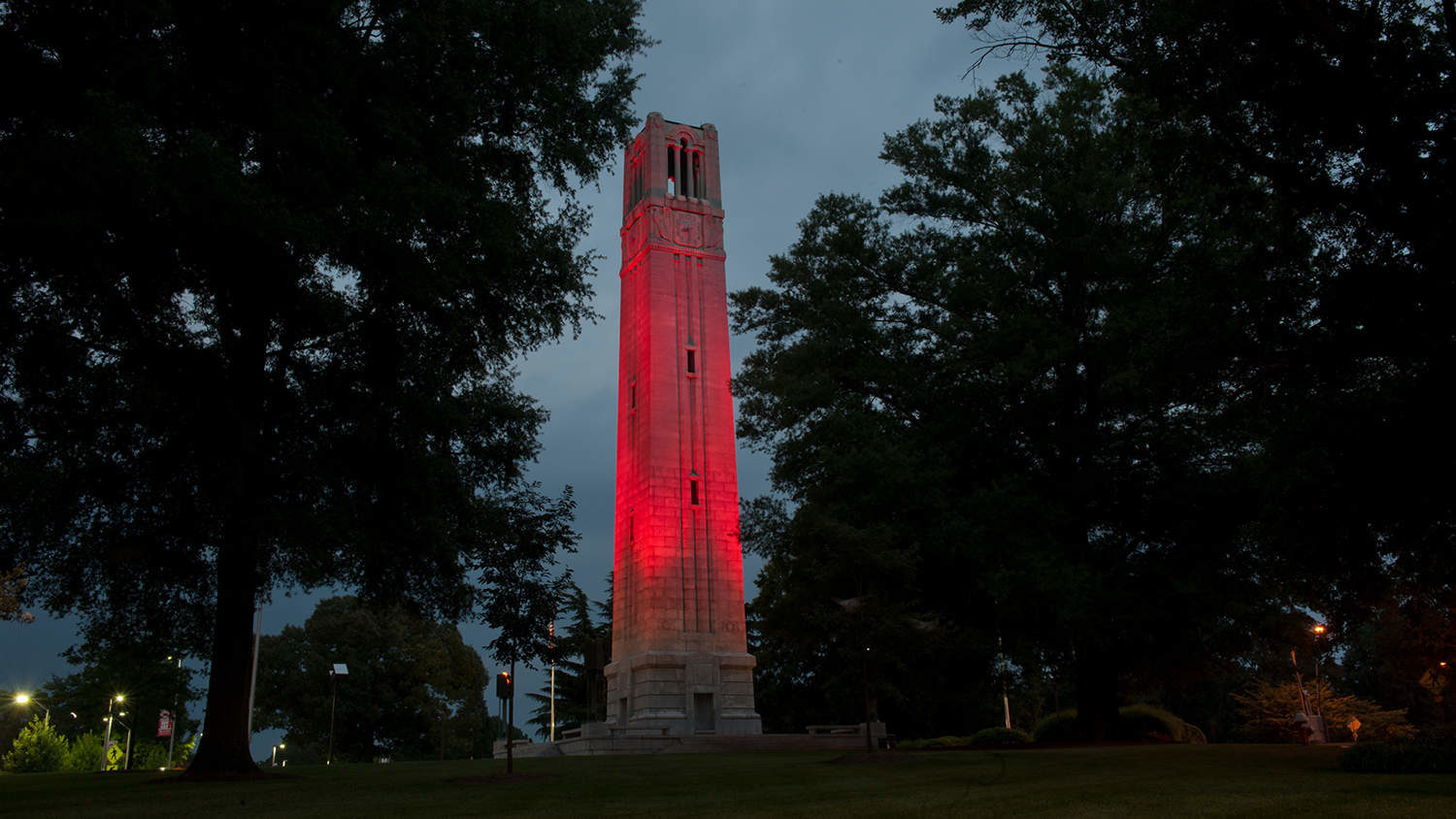 The NC State Belltower lit red against a night sky