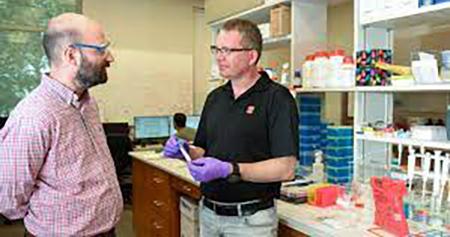 Michael Bereman and David Muddiman conversing in the lab