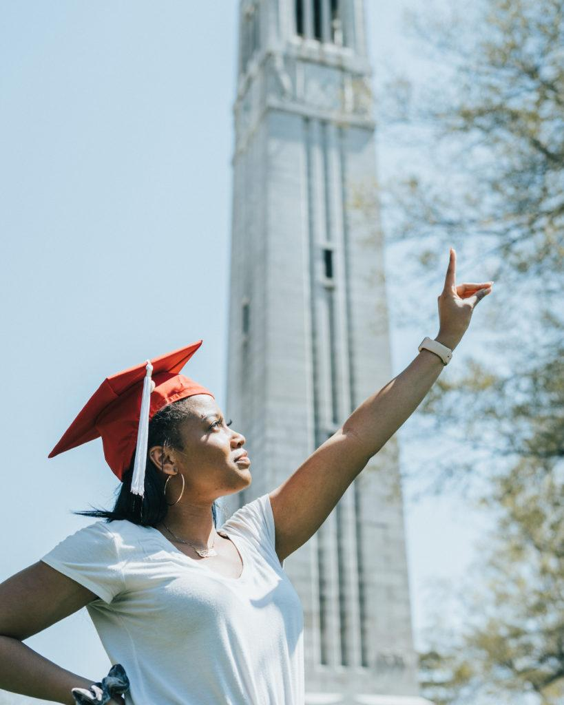 A student wearing graduation cap making the wolf sign and the bell tower in the background