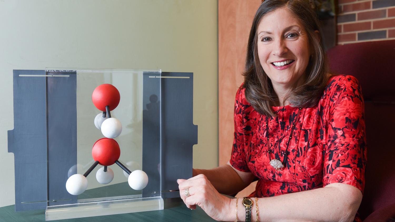 Maria Oliver-Hoyo next to a molecule reproduction