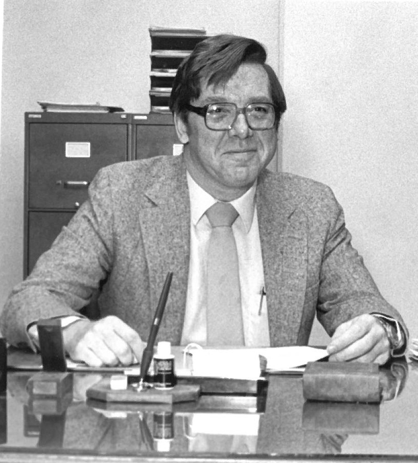 Kenneth Hanck in Black and White sitting at his desk