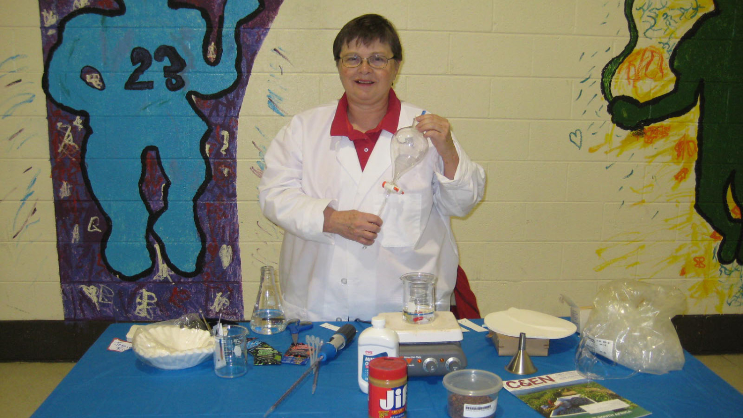 Jessie Rivers stands behind a table at a school career fair, conducting an experiment.