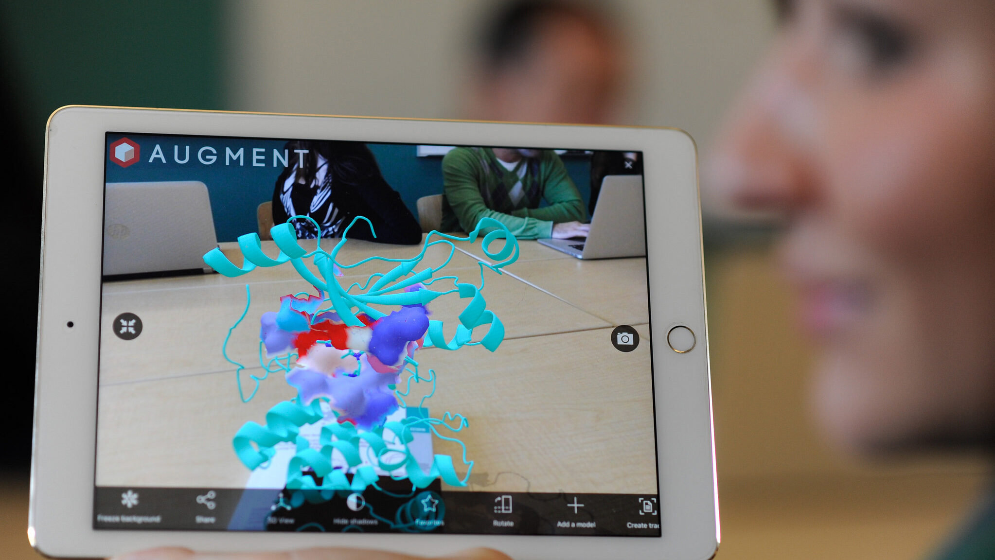 Bioinformatics student with augmented reality molecule on tablet