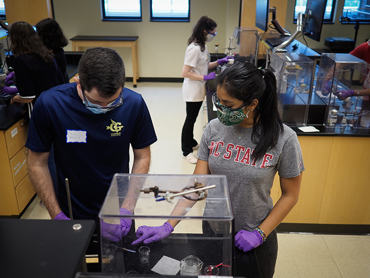 A student works closely with a graduate student TA to analyze the product of a reaction during the Organic Chemistry lab session.