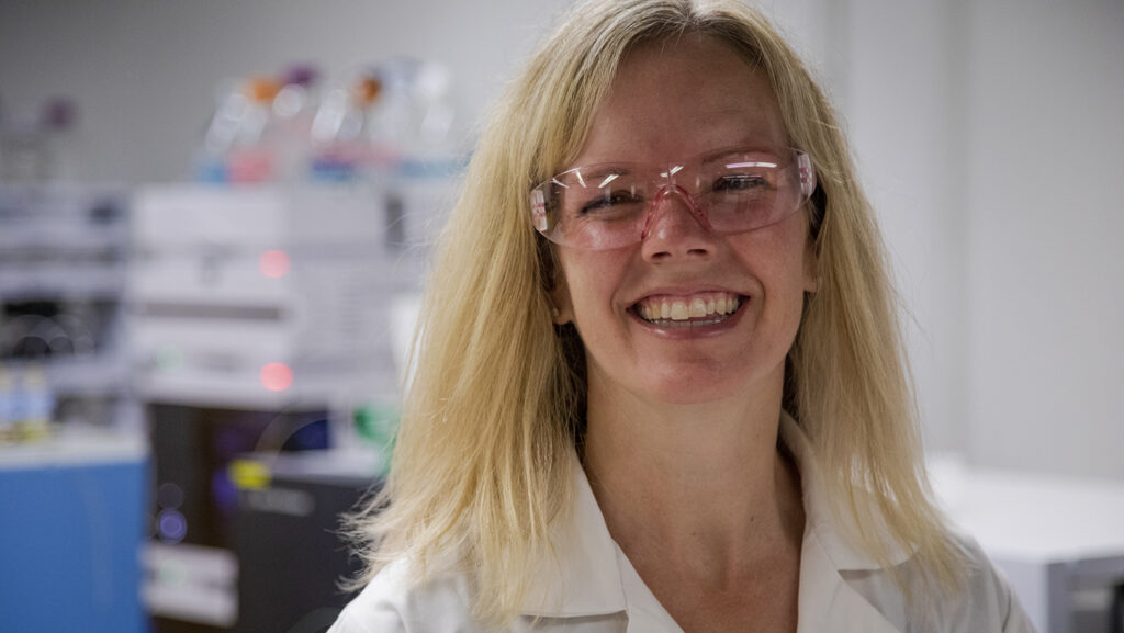 Dr. Erin Baker wearing goggles and a lab coat smiling