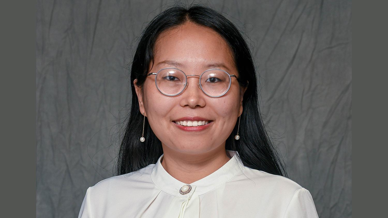 Hellena Bai wearing eyeglasses and a white button-up shirt Headshot